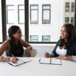 Two women smiling and having discussion in Boardroom
